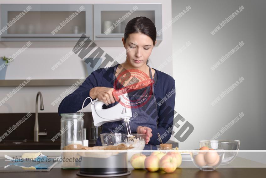 Junge Frau nutzt einen Handmixer